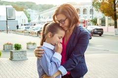 慰问她哭泣的女儿的母亲 都市的背景 图库摄影