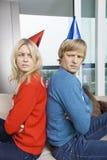 懊恼夫妇侧视图在圣诞节的毛线衣和紧接坐党的帽子的在家 免版税库存照片