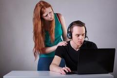 懊恼女孩她的打计算机游戏的伙伴 库存照片
