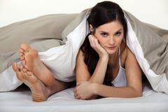 懊恼妇女在床上 图库摄影