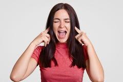 懊恼深色的妇女要求停止这声音,有两个食指的pluggs耳朵,愤怒惊叹,保持眼睛被关闭的,穿戴的加州 库存照片