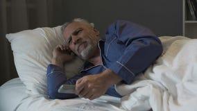 懊恼领抚恤金者遭受的失眠和紧张地交换的电视频道 免版税库存图片