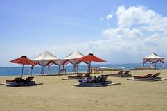 懒人椅子和遮阳伞在沙子在巴厘岛靠岸 免版税库存照片