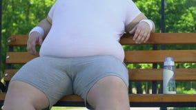 懒惰人坐抚摸他的大肥胖腹部的长凳而不是去体育的 股票录像