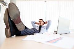 懒惰商人在书桌上把他的腿放 免版税库存照片