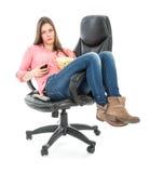 懒惰妇女开会在一把扶手椅子延长用玉米花和饮料 图库摄影