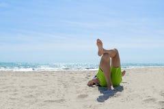 懒惰时间 人说谎腿对在海海滩的腿在一个夏日 库存图片