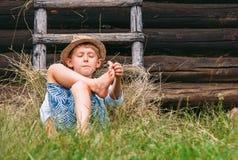 懒惰男孩在草在谷仓下-在计数的粗心大意的夏天在 免版税库存照片