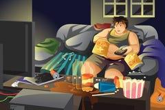 懒惰食人的土豆片和观看的电视 库存照片
