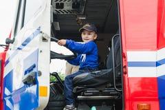 戈尔基,白俄罗斯- 2018年7月25日:男孩在后在一个红色汽车急救工作112坐方向盘一个假日在公园 免版税库存照片