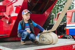 戈尔基,白俄罗斯- 2018年7月25日:男孩在急救工作112的红色汽车使用一个假日在公园在一个夏日 免版税库存照片