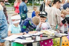 戈尔基,白俄罗斯- 2018年7月25日:两个小蒙住眼睛的男孩在桌上的纸画,并且一个小男孩膨胀在总和的一个气球 库存照片