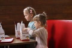 戈梅利,白俄罗斯- 2017年10月28日:咖啡馆的孩子打开在礼物盒的食物 库存图片