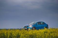戈梅利,白俄罗斯- 2018年5月15日:里诺摇石蓝色汽车在领域停放了反对风雨如磐的天空 免版税库存图片