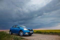 戈梅利,白俄罗斯- 2018年5月15日:里诺摇石蓝色汽车在领域停放了反对风雨如磐的天空 图库摄影