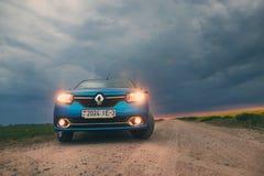 戈梅利,白俄罗斯- 2018年5月15日:里诺摇石蓝色汽车在领域停放了反对风雨如磐的天空 免版税库存照片