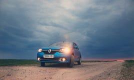 戈梅利,白俄罗斯- 2018年5月15日:里诺摇石蓝色汽车在领域停放了反对风雨如磐的天空 库存照片