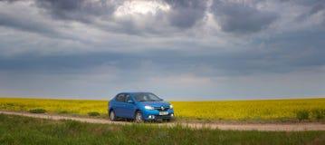 戈梅利,白俄罗斯- 2018年5月15日:里诺摇石蓝色汽车在领域停放了反对风雨如磐的天空 免版税图库摄影