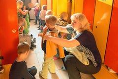 戈梅利,白俄罗斯- 2016年10月3日:三岁小孩为步行装饰在家庭教师帮助下 托儿所119 库存图片