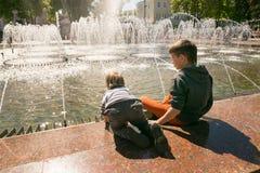 戈梅利,白俄罗斯- 2017年5月14日:儿童游戏用在一个城市喷泉附近的水在市戈梅利 免版税库存照片