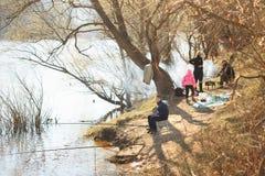 戈梅利,白俄罗斯- 2017年4月9日:家庭野餐本质上由河的 钓鱼与烤肉一起 免版税库存图片