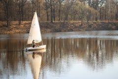 戈梅利,白俄罗斯- 2017年4月9日:有风帆的一条小船沿河在春天游泳 免版税库存图片