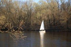 戈梅利,白俄罗斯- 2017年4月9日:有风帆的一条小船沿河在春天游泳 库存照片