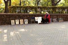 戈梅利,白俄罗斯- 2016年10月3日:街道艺术家在城市公园绘一张画象 库存照片