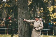 戈梅利,白俄罗斯 Reenactor以革命战士射击Nagant M1895左轮手枪的形式在庆祝的世纪  免版税库存照片