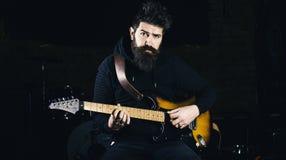 戏剧吉他概念 有胡子戏剧电吉他乐器的音乐家 库存照片