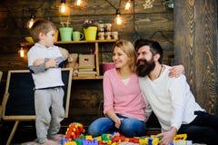 戏剧概念 有母亲的小孩和父亲使用与玩具砖 创造性的家庭戏剧 使用的最佳的地方 库存照片