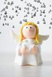 戏弄与书唱歌背景音乐的圣诞节天使 库存图片