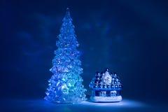 戏弄发光与美丽的阴影北极光的圣诞树在从一个童话的房子附近在深蓝背景 免版税库存图片