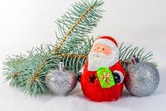 戏弄圣诞老人和球在圣诞树分支 免版税库存照片