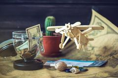 戏弄在一张世界地图的木飞机与色的石头和壳从海一个减速火箭的样式的 免版税库存图片