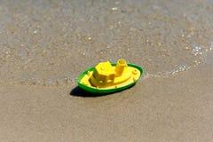 戏弄在海的湿沙子的小船 海滩节假日凉鞋海运夏天海浪 小船旅行 免版税库存照片