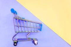 戏弄在淡色黄色和蓝色背景的推车 免版税库存照片