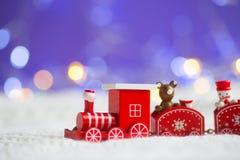 戏弄在白色被编织的织品的红色木机车在紫色后面 库存照片