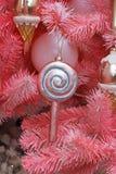 戏弄垂悬在桃红色圣诞树分支的棒棒糖  免版税库存图片