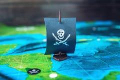 戏弄小船海盗旗子头骨和骨头在运动场手工制造棋的世界地图 免版税库存图片