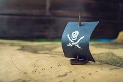 戏弄小船海盗旗子头骨和骨头在运动场手工制造棋的世界地图 免版税库存照片