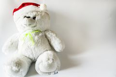 戏弄戴圣诞老人帽子,在轻的背景的玩具熊 免版税库存图片