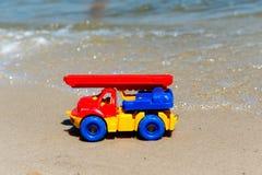 戏弄有景气的卡车在湿沙子 海滩节假日凉鞋海运夏天海浪 特别缩样 库存图片