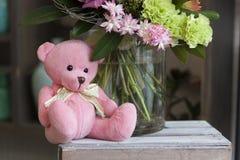 戏弄桃红色玩具熊坐一个木箱 免版税图库摄影