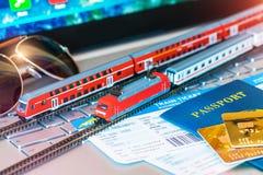 戏弄火车、票、护照和银行卡在膝上型计算机或笔记本 免版税库存照片