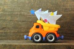 戏弄运载手工纸圣诞树的卡车反对概略的木背景 侧视图 圣诞树回收或处置, 库存照片