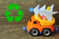 戏弄运载手工纸圣诞树的卡车反对概略的木背景 侧视图 圣诞树回收或处置, 免版税库存图片
