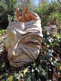戏曲面孔和手雕塑在庭院里 免版税库存照片