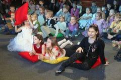 年轻戏迷 热心地观看儿童的圣诞节木偶剧场Smeshariki的孩子 库存照片