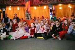 年轻戏迷 热心地观看儿童的圣诞节木偶剧场Smeshariki的孩子 免版税库存图片